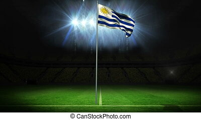 Uruguay national flag waving on flagpole against football...