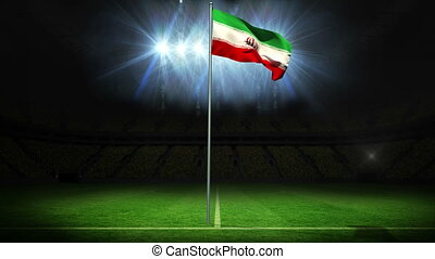 Iran national flag waving on flagpole against football pitch...
