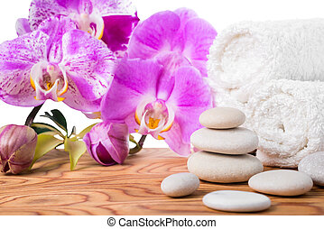Spa setting with stones, lilac orchids and towels is isolated on