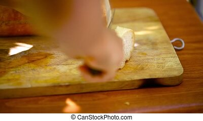 Baker Slicing french Bread on a Cutting Board. Macro...