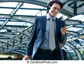 talking on mobile phone in subway - happy businessman...