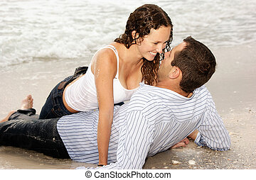 beautiful couple laying on beach smiling at each other