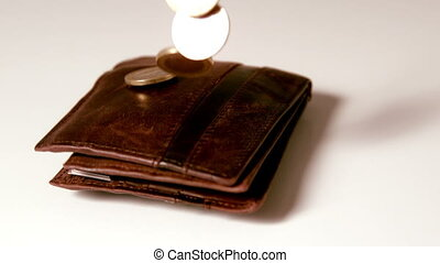 Euro coins falling over brown leather wallet on white...