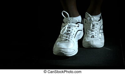 Legs in running shoes jogging against black background in...