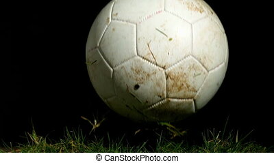Dirty football bouncing on grass in slow motion