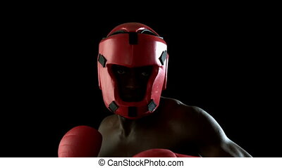 Tough boxer punching with red gloves in slow motion