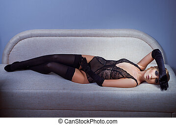 woman in black stockings lying on the sofa