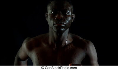 Shirtless man jogging against black background in slow...