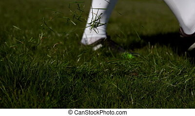 Football player kicking the ball on grass in slow motion