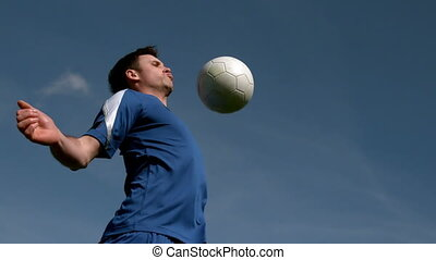 Football player chesting the ball under blue sky in slow...