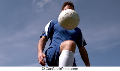Football player controlling the ball under blue sky in slow...