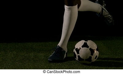 Football player kicking the ball in slow motion