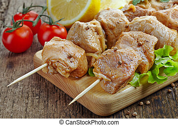 raw marinated pork kebab meat pieces on wooden skewers