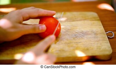 Female hands sliced tomato on a wooden board. Macro video...
