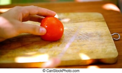 Female hands sliced tomato on a wooden board. Macro fast...