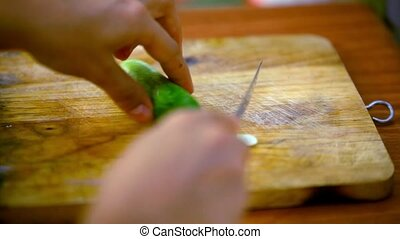 Female hands cutting cucumber on wooden board. Macro video....