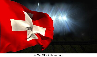 Large swiss national flag waving on black background with...