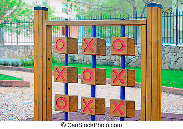 noughts and crosses - wooden tic tac toe in a green park