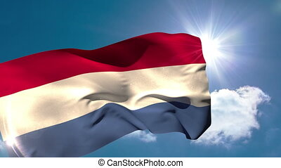 Dutch national flag blowing in the breeze on blue sky...
