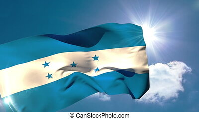 Honduran national flag blowing in the breeze on blue sky...