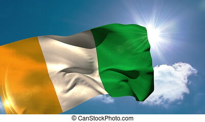Ivory coast national flag blowing in the breeze on blue sky...