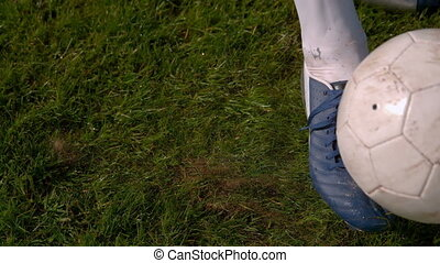Football player kicking the ball on pitch in slow motion