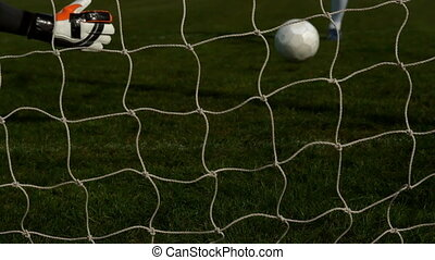 Goalkeeper in red letting in a goal during a game in slow...