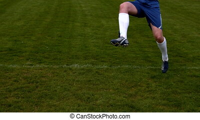 Football player in blue kicking the ball on pitch in slow...