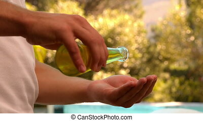 Masseuse pouring oil onto hands
