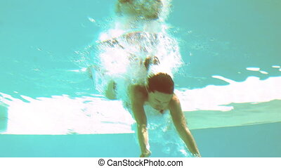 Brunette diving underwater in swimming pool in slow motion