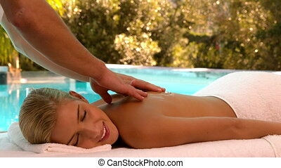 Masseuse rubbing oil into blondes back poolside in slow...