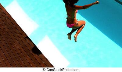 Woman in pink bikini jumping into pool