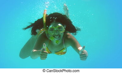 Happy brunette wearing snorkel underwater