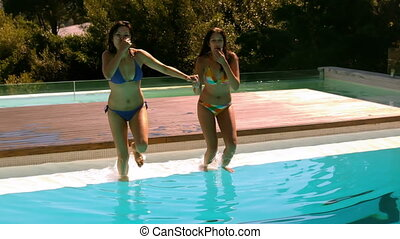 Happy friends jumping into swimming pool together in slow...