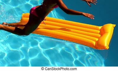 Woman in pink bikini jumping into swimming pool onto lilo in...