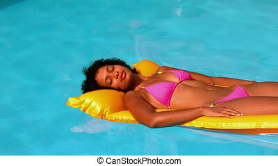 Happy woman in pink bikini relaxing on lilo in swimming pool...