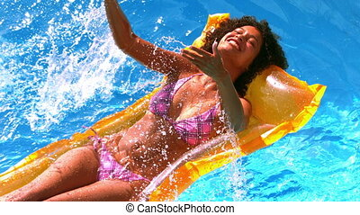 Happy woman splashing on lilo in swimming pool in slow...
