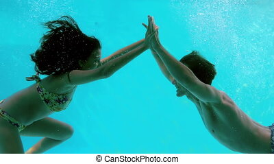 Happy couple holding hands underwater in swimming pool in...