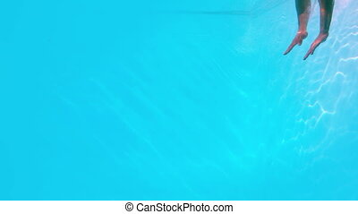 Fit man swimming underwater in the pool in slow motion