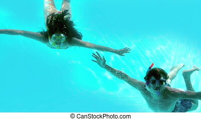 Happy couple wearing snorkels underwater in swimming pool in...