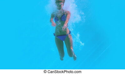Fit woman jumping into swimming pool