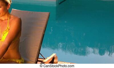 Sexy woman in yellow bikini relaxing