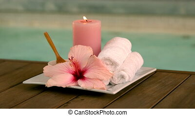 Beauty treatments and candle poolside with lily in slow...