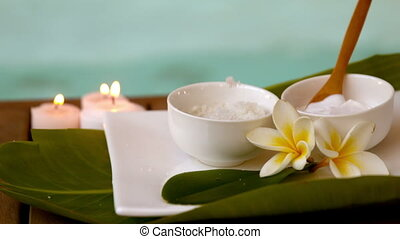 Beauty treatments in bowls poolside with flowers in slow...