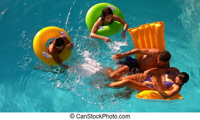 Friends having fun and splashing in pool together in slow...