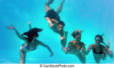Friends waving at camera underwater in swimming pool...