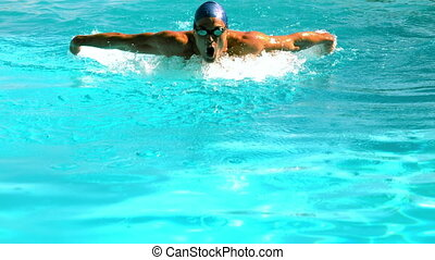 Fit swimmer doing the butterfly stroke in the swimming pool...