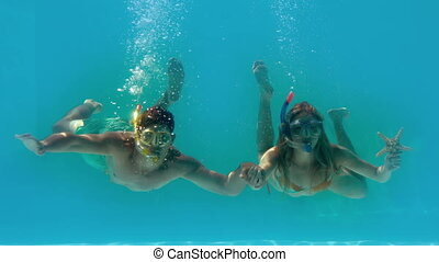 Couple wearing snorkels holding starfish underwater in slow...