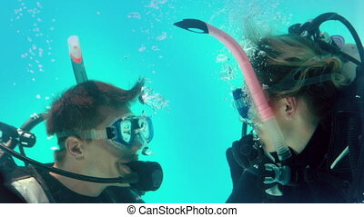 Couple in scuba gear looking at each other underwater in...