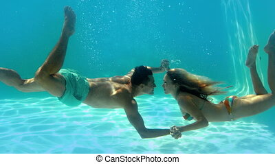 Couple kissing underwater in the swimming pool in slow...